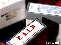"Rubber stamps reading ""Paid"" and ""approved"""