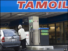 A woman refuels her car at a Tamoil gas station, in Geneva