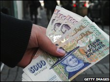 A bank customer holds a handful of Icelandic crowns in Rekyavik (8/10/2008)