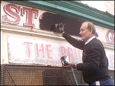 Vale of Clwyd MP Chris Ruane paints out the sign in Rhyl