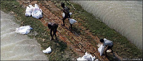 Men retrieving food aid from a flood defence (Getty Images)