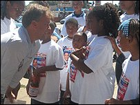 Matt Frei talking to children raising funs for Obama