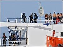 القراصنة على سطح السفينة  و مجموعة من أفراد الطاقم على اليمين