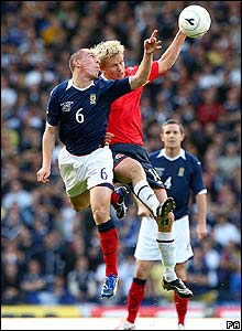 Scottish midfielder Scott Brown competes in an aerial challenge with Steffen Iversen