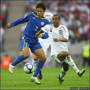 Striker Tanat Nusserbayev tussles with England defender Ashley Cole