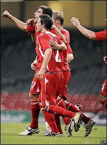 Ched Evans celebrates with his Wales team-mates