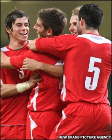 Ched Evans is congratulated after Wales get their second goal