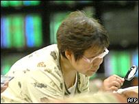 Una mujer mira con lupa los resultados de la bolsa