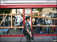 Israeli police officer passes vandalised shop