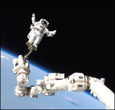 An astronaut attatched to an arm on the International Space Station