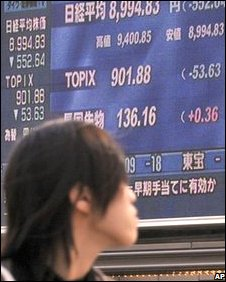 A young man passes an electric market board in Tokyo, 16 October