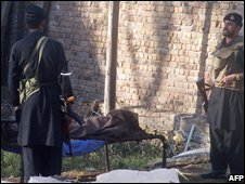 Pakistani security personnel stand next to a body at the police station in Mingora, Pakistan, on 16/10/2008