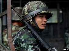 A Thai soldier looks out as he sits with others in the back of an army truck near the Cambodia border