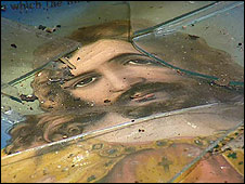 Religious painting covered in broken glass