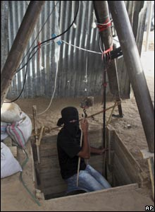 A smuggler being lowered into the tunnel using a pulley system
