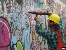 A worker uses a drill to prepare a section of the Berlin Wall's East Side Gallery for restoration (15/10/208)