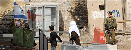 A Palestinian woman passes through an Israeli checkpoint in H2