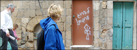 "Visitors to Hebron walk past graffiti saying ""kill Arabs"""