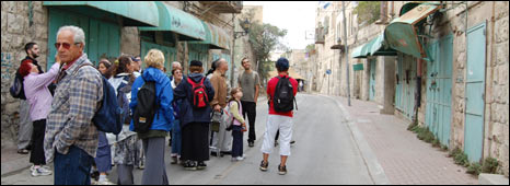 Tourists in empty Hebron street, formerly filled with Palestinian shops