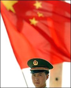 Policeman in front of a Chinese flag