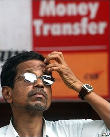 An Indian investor watches share prices on a digital broadcast screen on the facade of the Bombay Stock Exchange