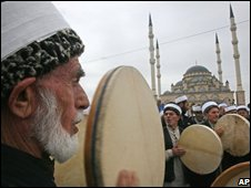 Local Muslims play national instruments outside the Heart of Chechnya mosque