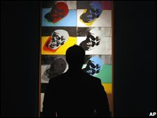 A man silhouetted in front of the Skulls painting