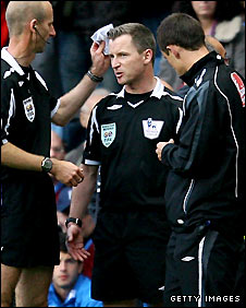 Assistant referee Phil Sharp receives treatment