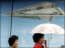 South Korean woman walks past a poster of a paper airplane made of a US dollar (5 September 2008)