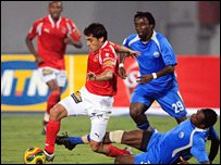 Ahly's Ahmed Hassan (left) in a tussle with Enyimba's Monday Osagie (right)