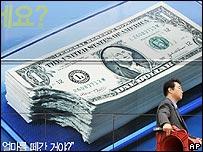 Trabajador surcoreano pasa frente a un afiche publicitario de un banco en Seúl