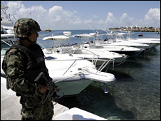 A Mexican navy sailor guards speedboats seized in Isla Mujeres that were being used to traffic Cuban migrants