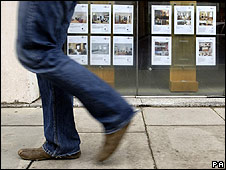 Man walks past estate agent