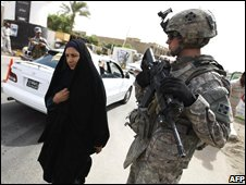 An Iraqi woman walks past a US solider in the Dora district of Baghdad (09/10/2008)