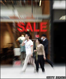 People walking past a SALE sign