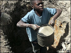 A boy lifts a tin of water from a hole in Harare in September 2008