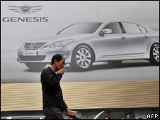 A man walks in front of advertisement for Hyundai car