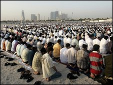 Muslims praying and Dubai skyline