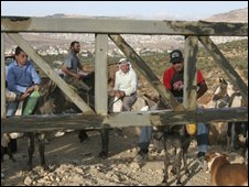 Olive farmers wait at an Israeli checkpoint in Nablus