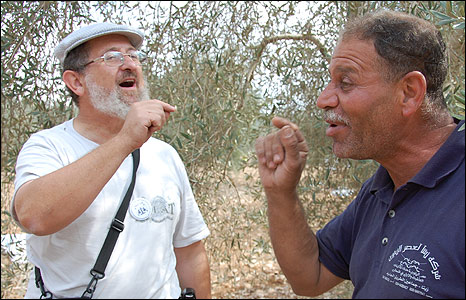 Rabbi Yehiel Grenimann and Abu Nimer Shtawie discuss religion during olive harvest