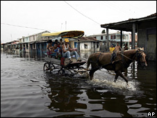 Residents drive a horse cart through a flooded street in Batabano, Cuba (11 September 2008)