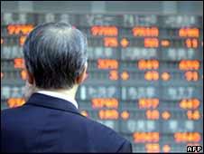 Man watches stock figures in Tokyo