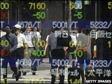 People walking in front of a Japanese shareprice board