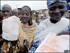 Angry residents hold IDs as they wait outside a registration office in Ivory Coast, 14 October 2008