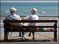 An older man and a woman sitting on a  bench by a beach
