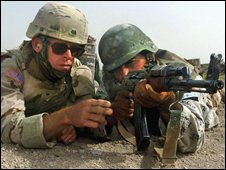 A US soldier training an Iraqi soldier