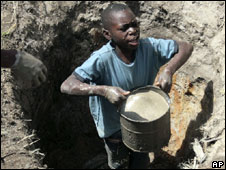 A boy lifts a bucket of water from a borehole in Harare