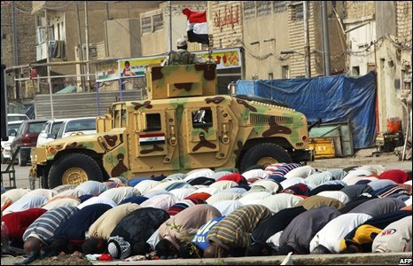 Iraqi army armoured vehicle behind Shia Muslims praying in Baghdad, Iraq