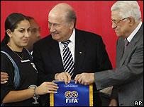El presidente de la FIFA, Sepp Blatter, y el presidente de la autoridad palestina, Mahmoud Abbas, posan con una jugadora palestina durante el acto inaugural de la liga femenina de fútbol en Ramala.