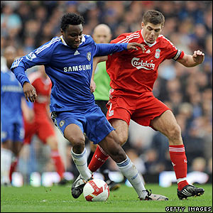 Mikel keeps the ball from Steven Gerrard